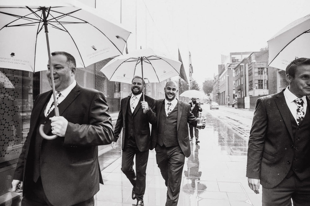 best men share umbrella on the street in the rain