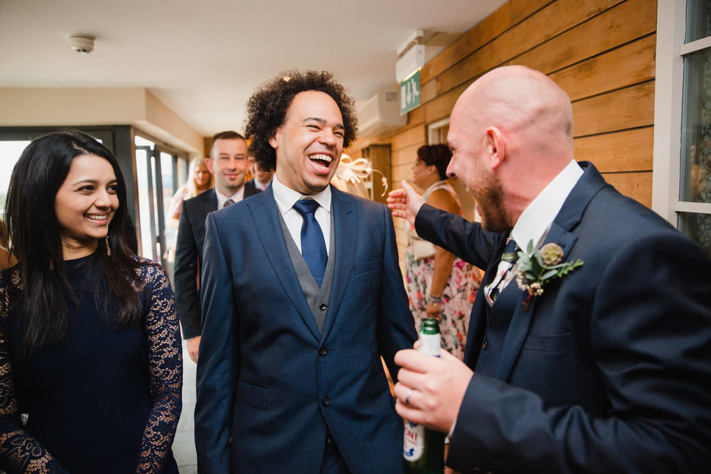 wedding guests laughing and joking together
