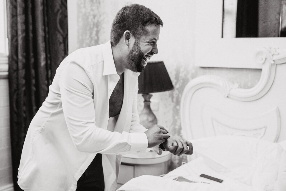 black and white photograph of groom laughing during preparation