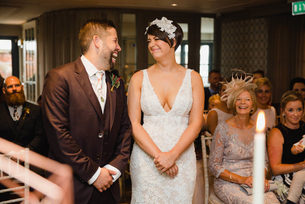 bride and groom laughing at top of aisle during ceremony