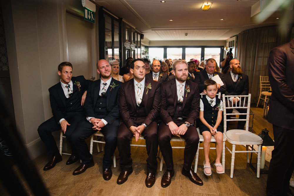 best men and ushers watching wedding vows being read