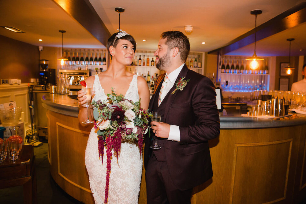 bride and groom pose with drinks and holding bouquets in hotel bar