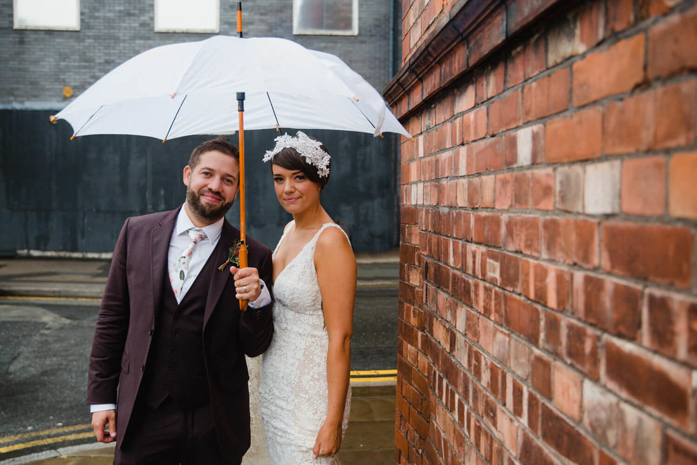 newly wedded couple pose under umbrella outside great john street