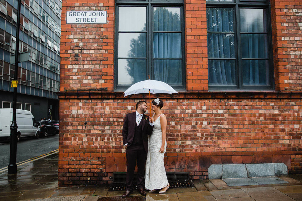happily wed couple under white umbrella laughing and joking on great john street