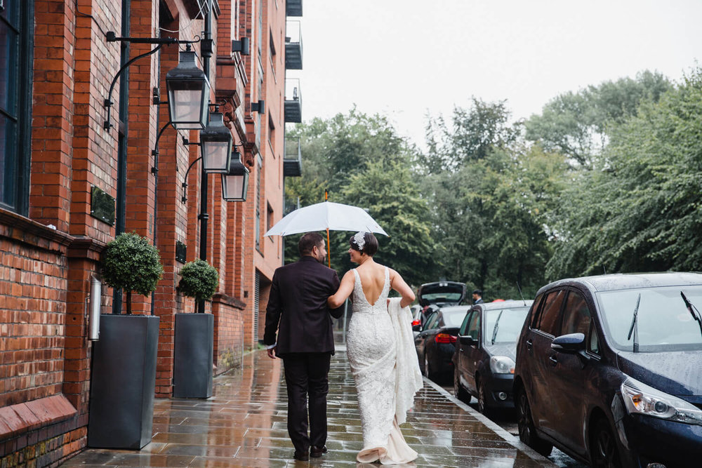 photograph taken from behind with bride and groom walking down street pavement together