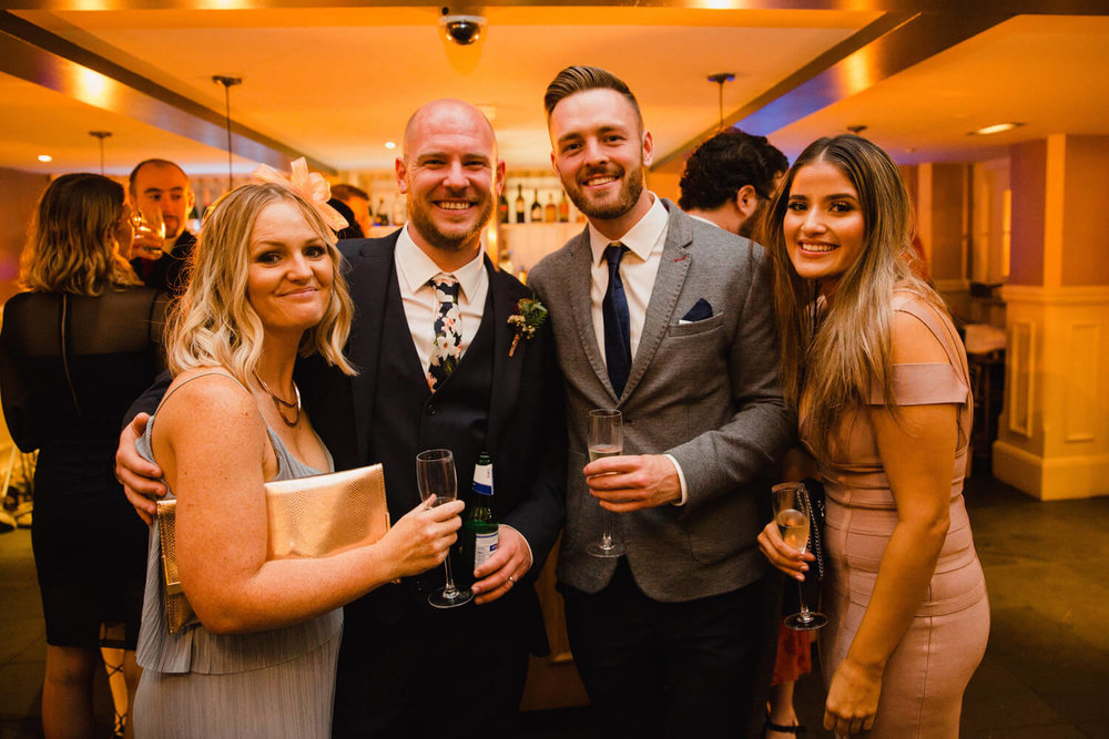 wedding guests pose to camera at bar of great john street hotel