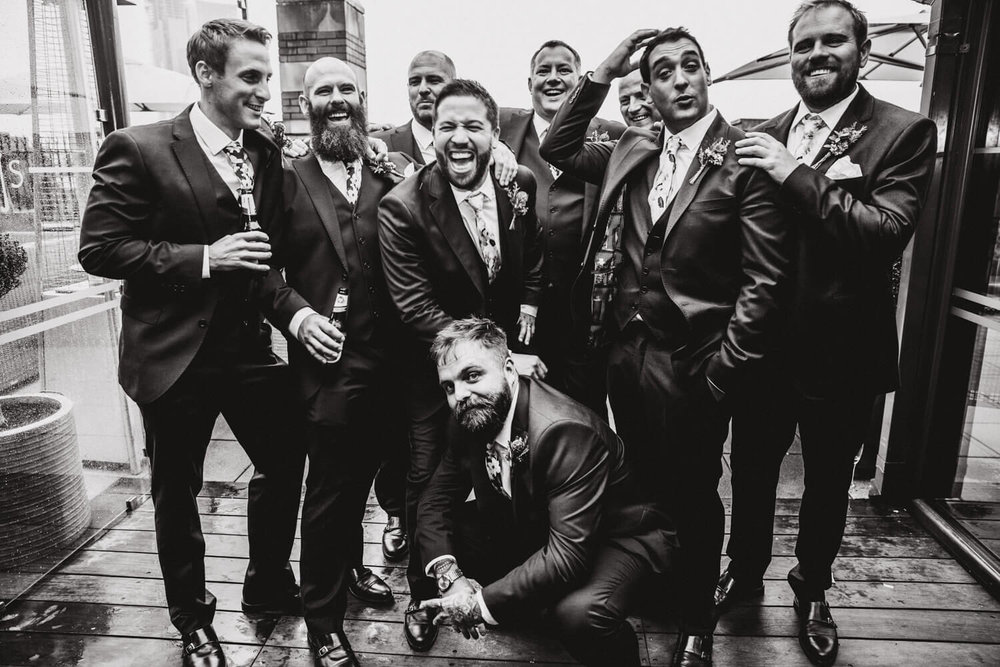black and white photograph of groomsmen together on roof terrace