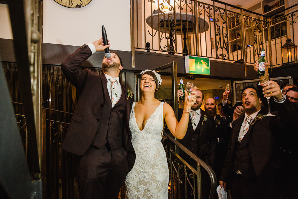 raising a toast with champagne and groom holding microphone to the air