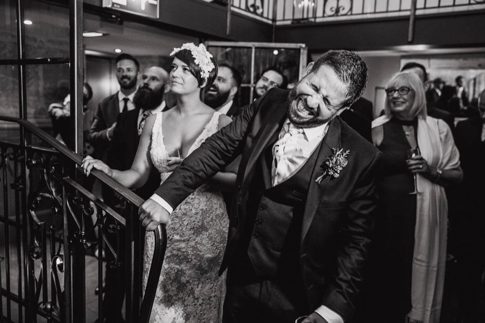 black and white photograph of groom cringing at best man speech