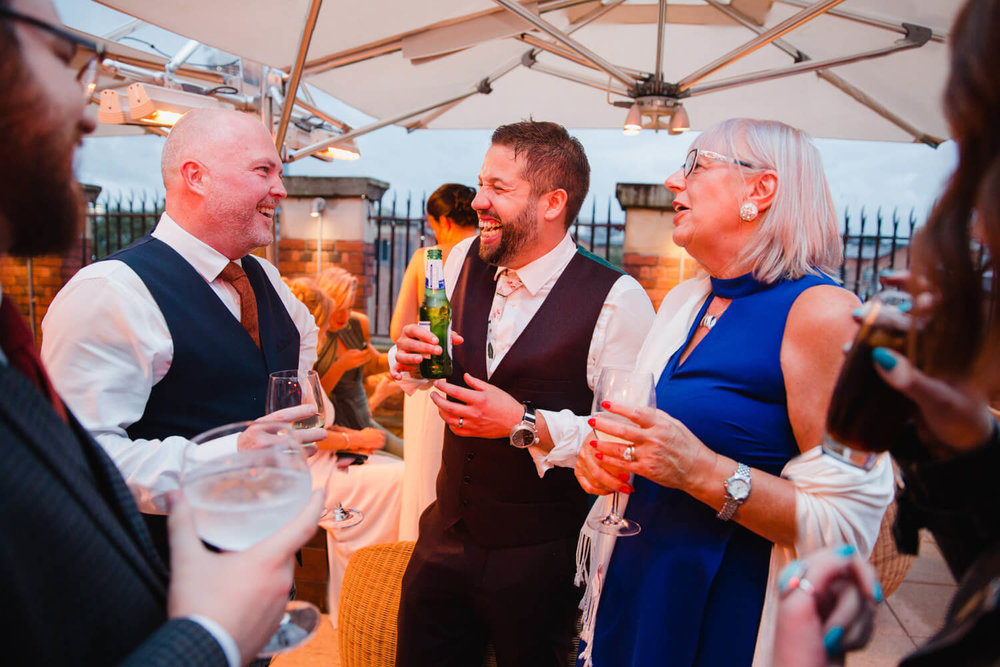 groom shares jokes and laughs with friends on roof terrace