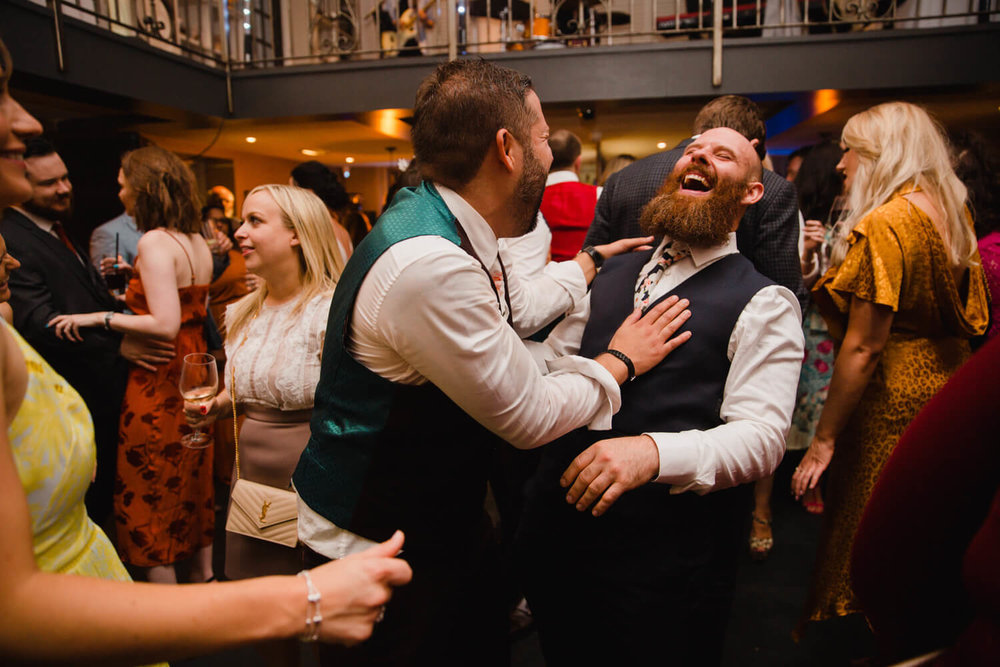 best man joking with groom on dance floor