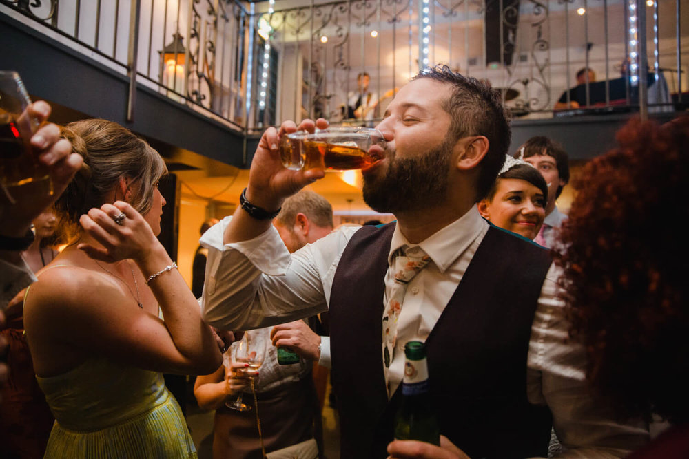 groom enjoys a drink after first dance at great john street