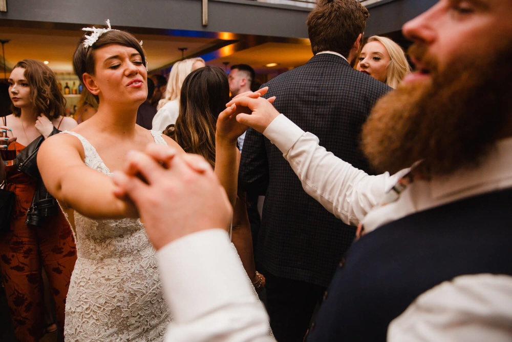 bride dances with best man after first dance