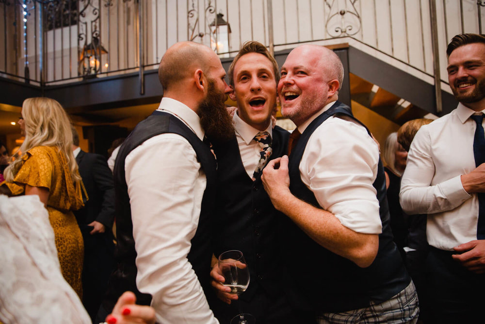 groomsmen enjoying dance together during party