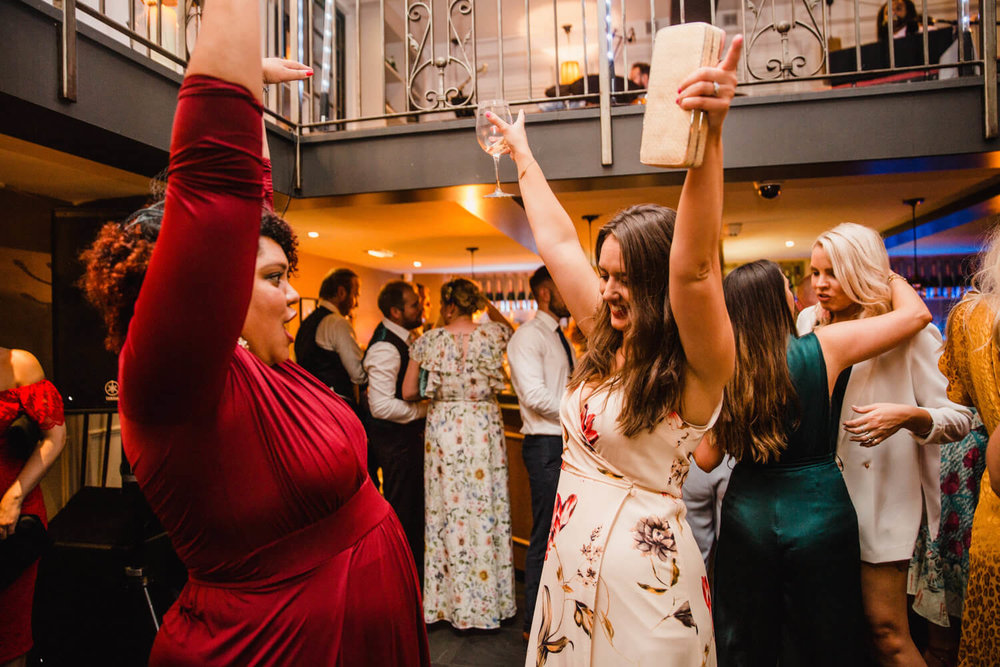 wedding guests with arms in air dancing to music