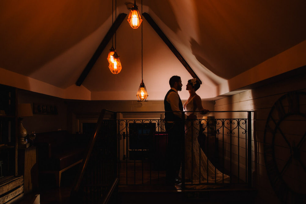 Low-lit silhouette portrait of bride and groom lit with festoons