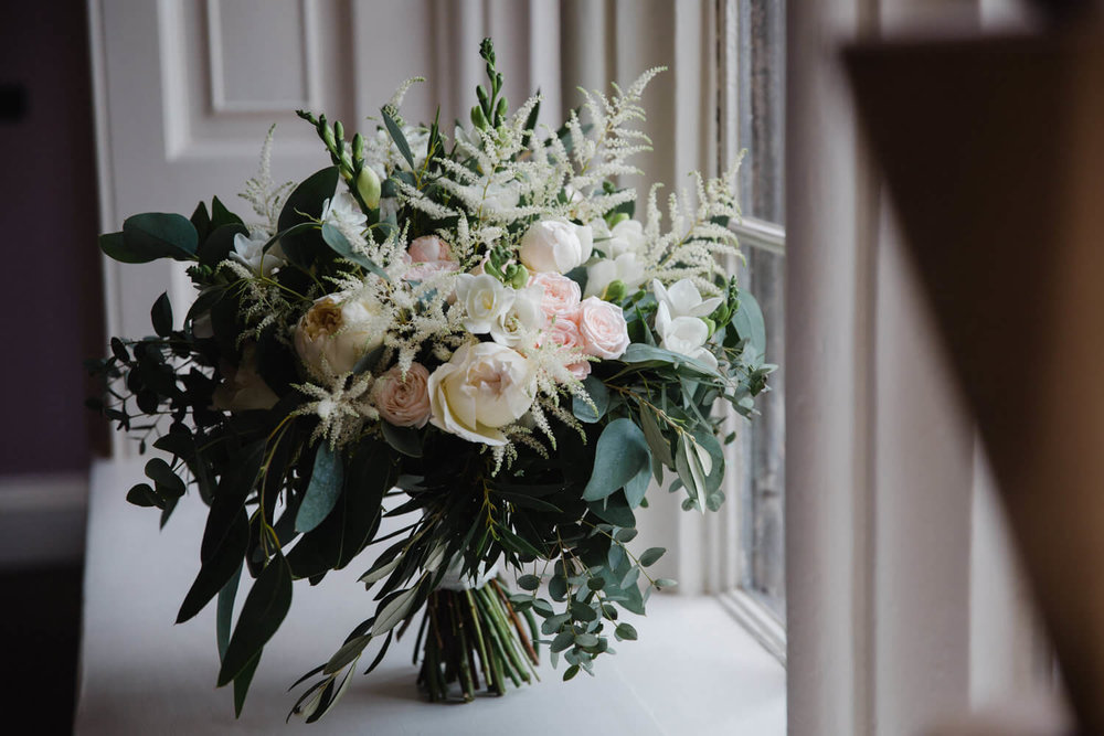 Wedding bouquet of flowers in window of Dorfold Hall