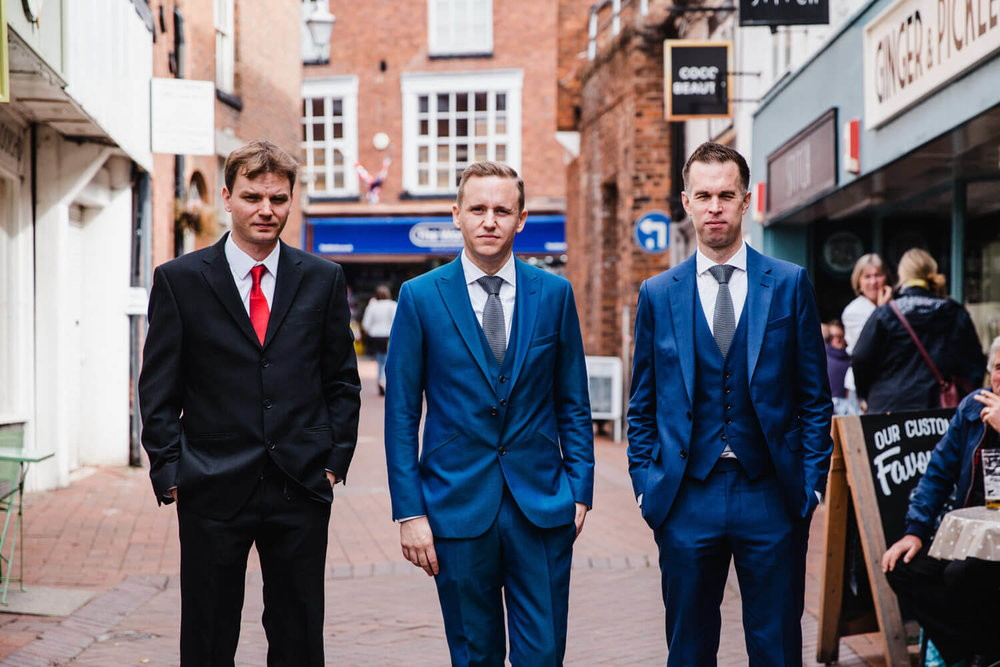 groomsmen walking down road to venue