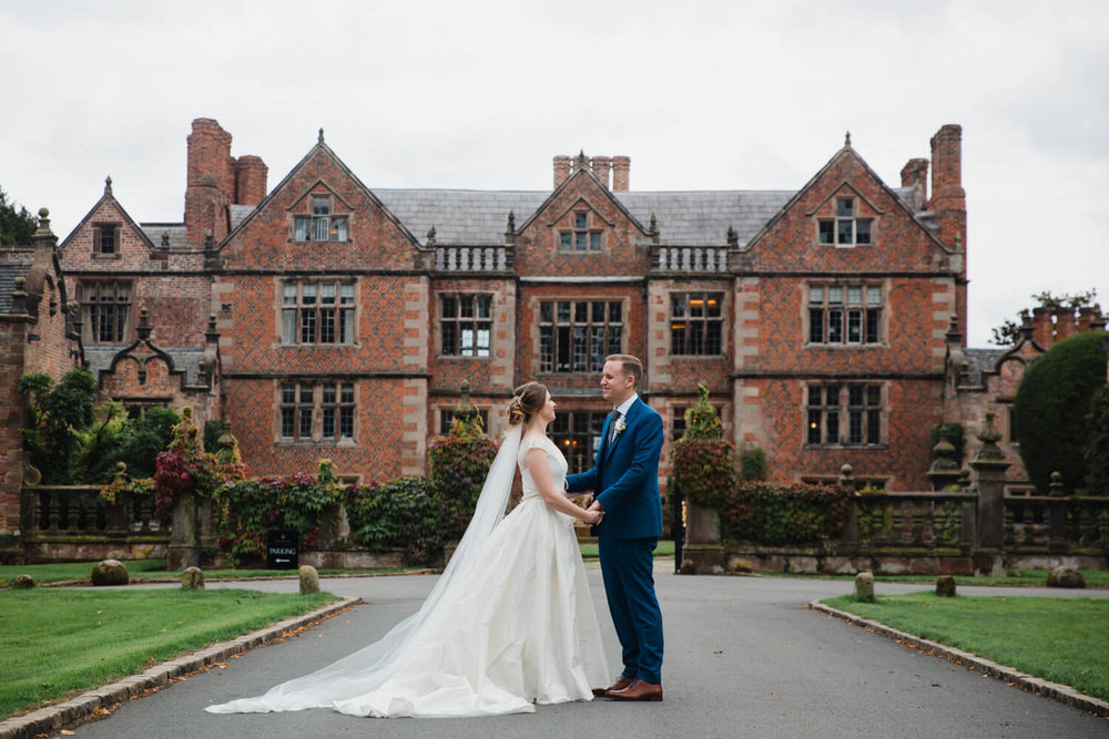 bride and groom holding hands in front of dorfold hall