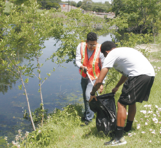 Yonathan Trejo, left, and DeShon Lee help clean up Lake Thunderduck.