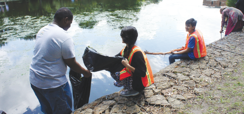 Edward Sesay, left, Larissa Rubio and Tony Prieto Loreto help pull trash out of Lake Thunderduck.
