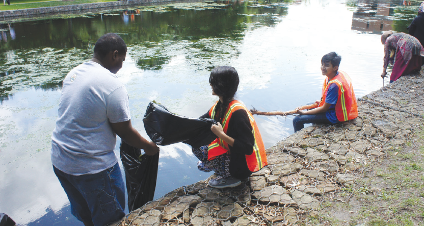 Edward Sesay, left, Larissa Rubio and Tony Prieto Loreto clean up campus during Earth Day