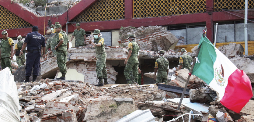 Soldiers remove debris from a partly collapsed municipal building felled by a massive earthquake in Juchitan, Oaxaca state, Mexico, Friday, Sept. 8.