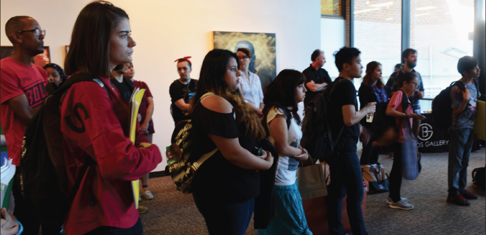"""Students listen as Spencer Evans speaks about his inspiration for """"The Veil's Farewell"""" in the Brazos Gallery on Sept. 21."""