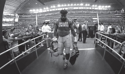 Dallas Cowboys running back Ezekiel Elliott walks off the field holding the jersey of Los Angeles Rams running back Todd Gurley after their game, Sunday, Oct. 1, 2017, in Arlington.