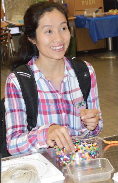 Tram Nguyen makes a bracelet.