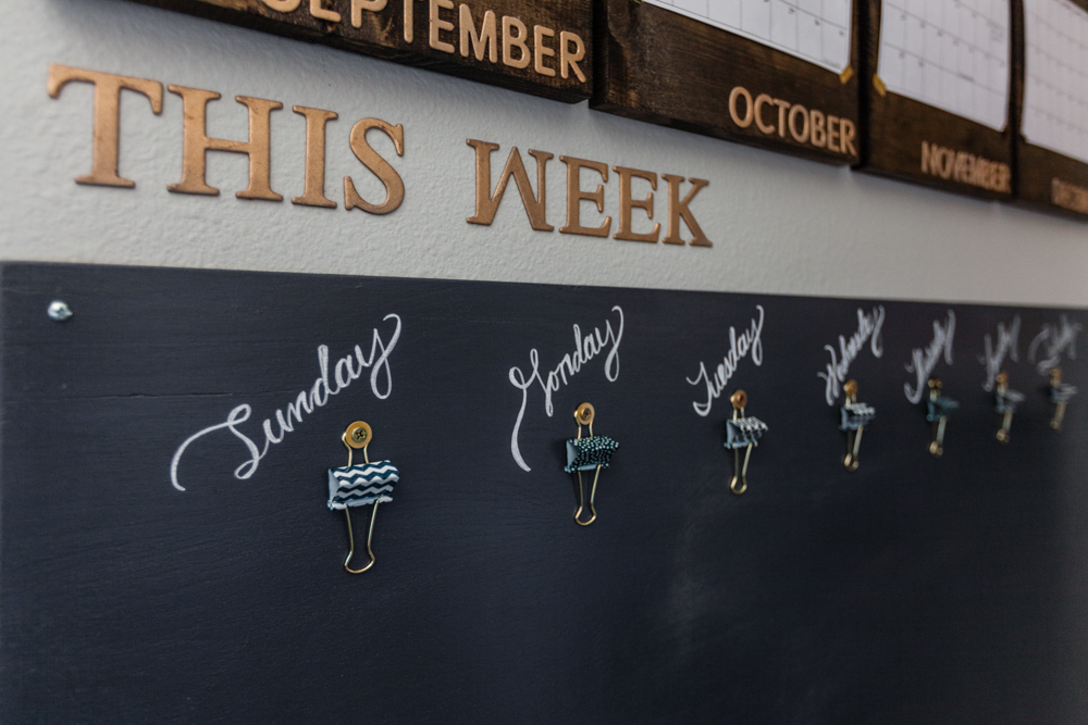 """One of my genius ideas to stay organized and on top of things. I always have """"genius"""" ideas.... I hope this one is the answer! A painted piece of birch plywood. Clips from Target with gold washers and screws from Home Depot. Hand-lettered days above each clip. Raised letters from Hobby Lobby, sprayed with gold spray paint."""