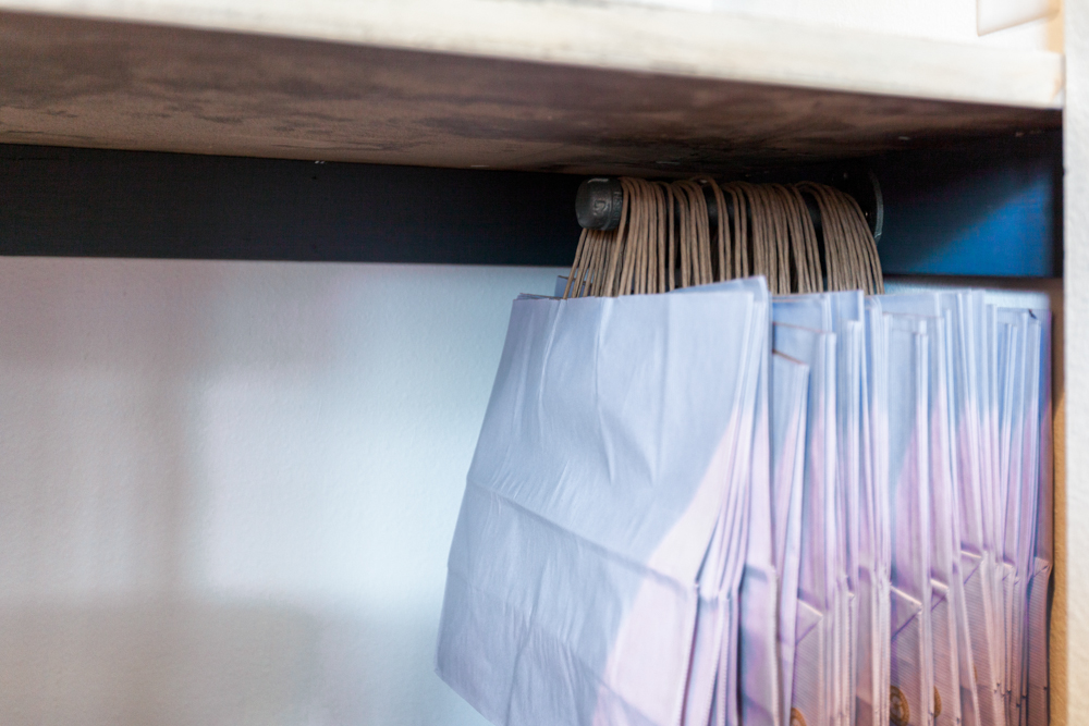 """A 8"""" galvanized pipe hung below the workspace to store my client bags."""