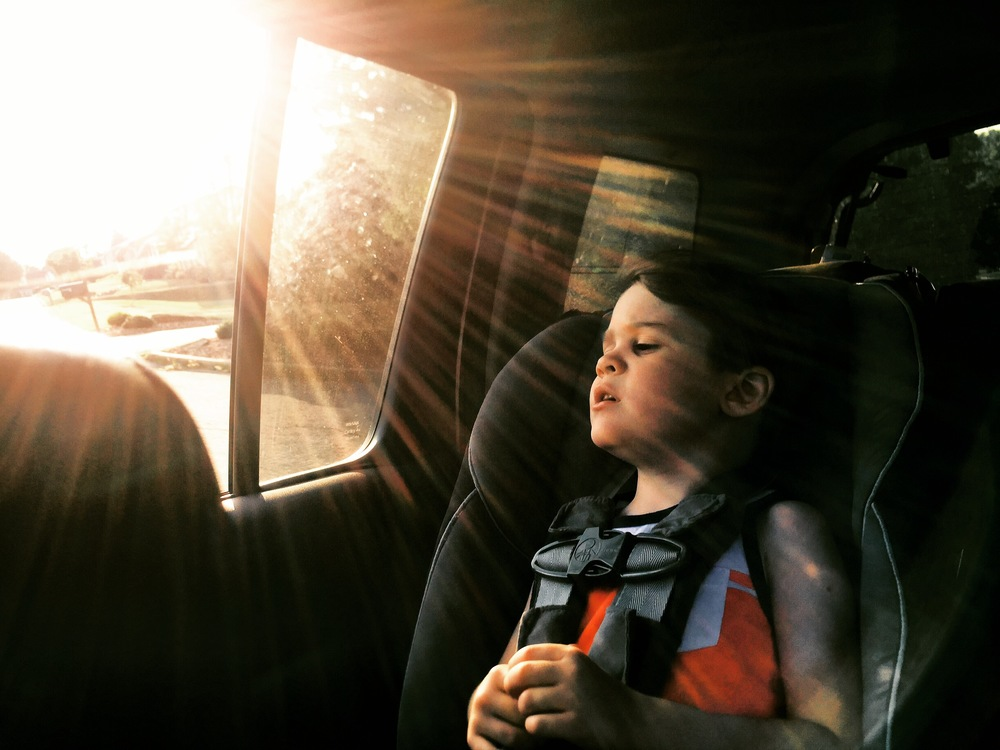 boy in car with wind and sun flare