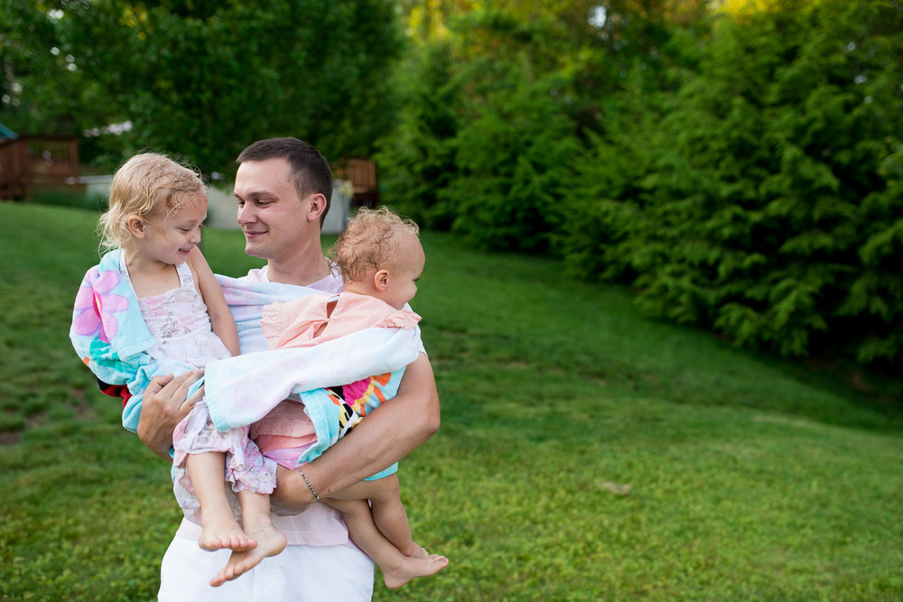dad holding daughters