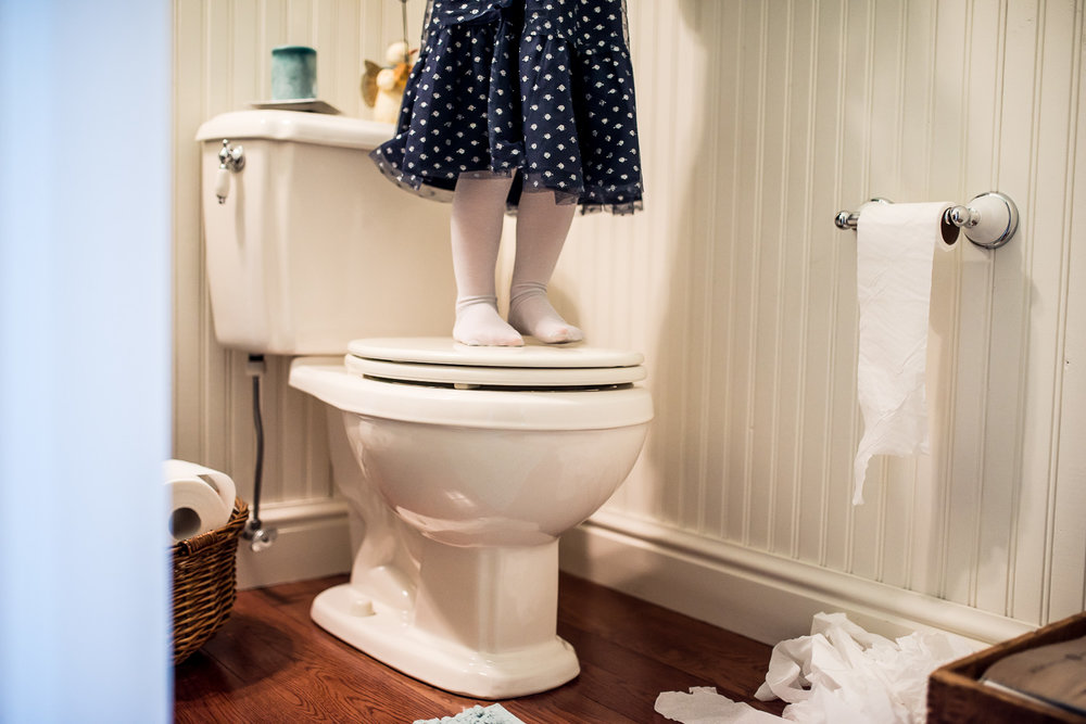 girl standing on toilet