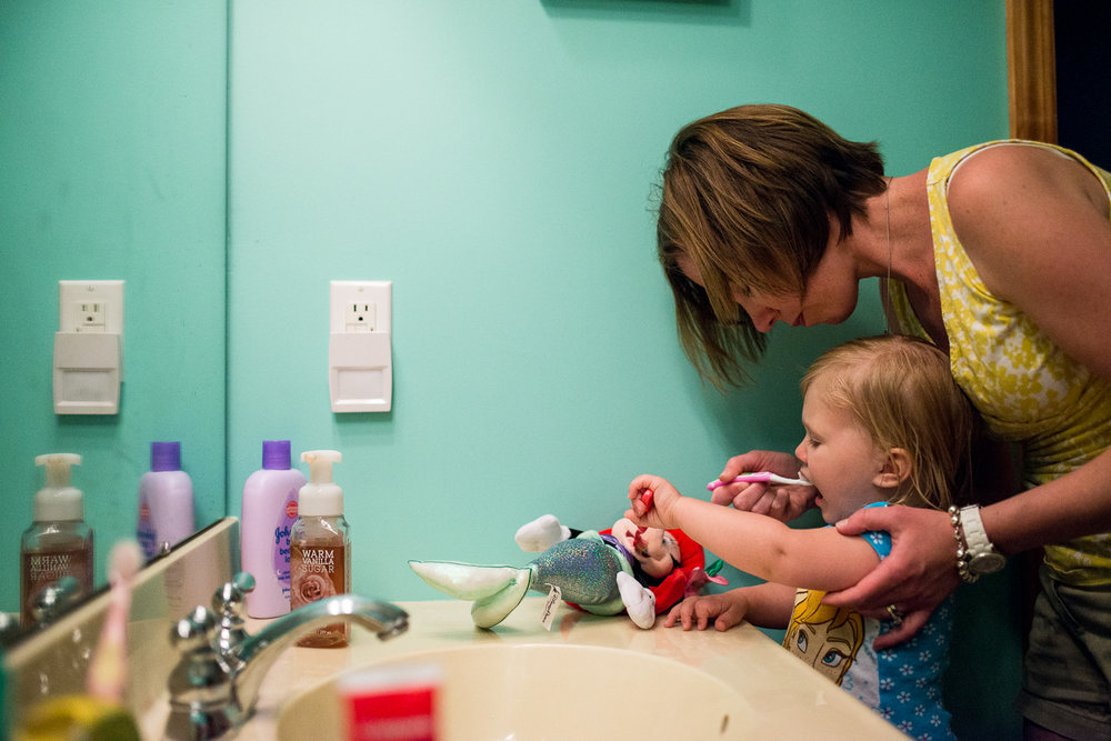 mom brushing child's teeth