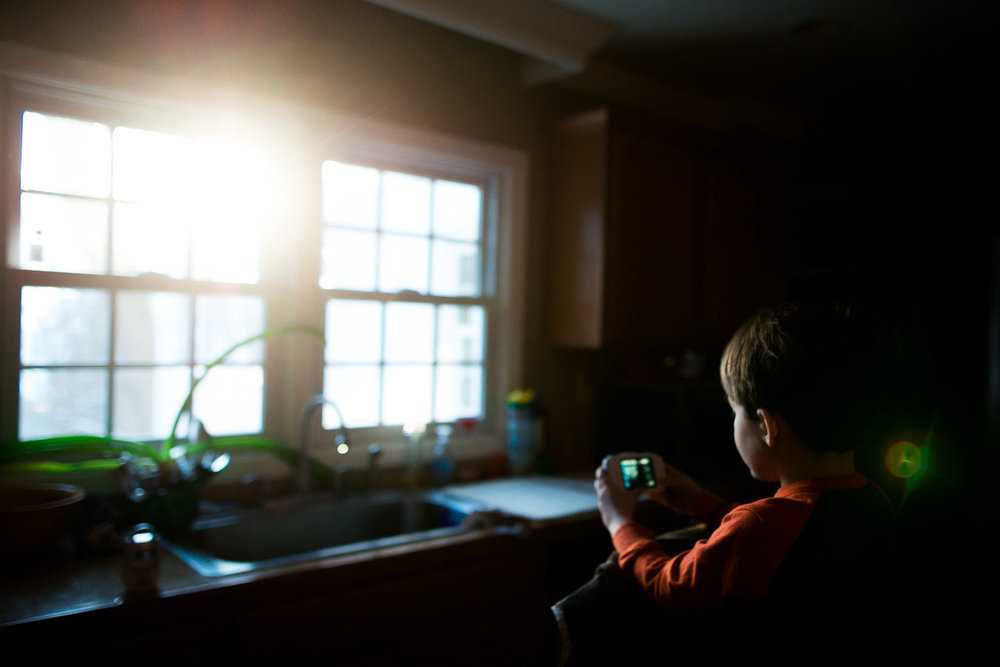 boy taking a picture of window light