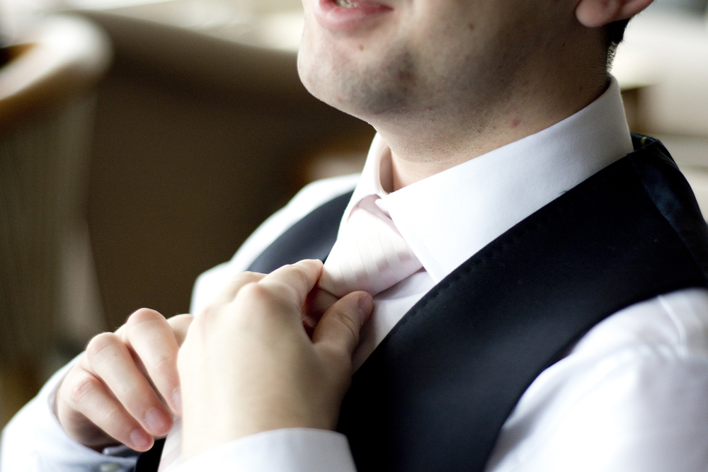 groom adjusts pink tie at The Greenbank Hotel Falmouth