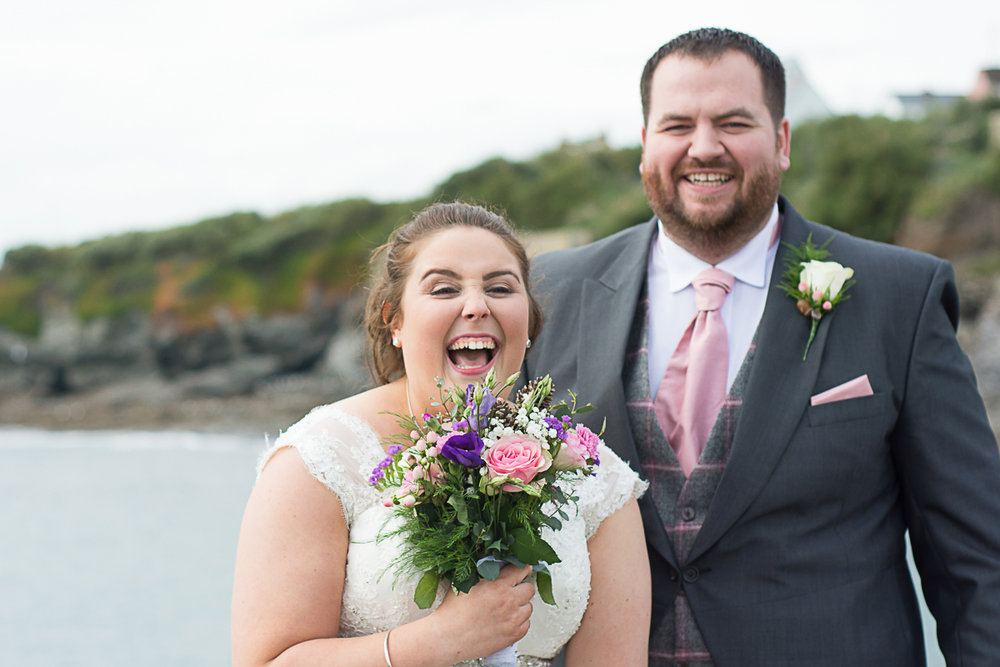 belly laughing bride and groom on Porthleven pier