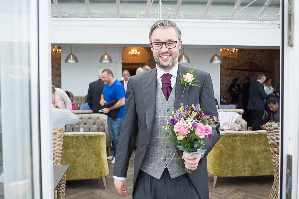 best man doing his duties and carrying the bouquet at carbis bay cornwall
