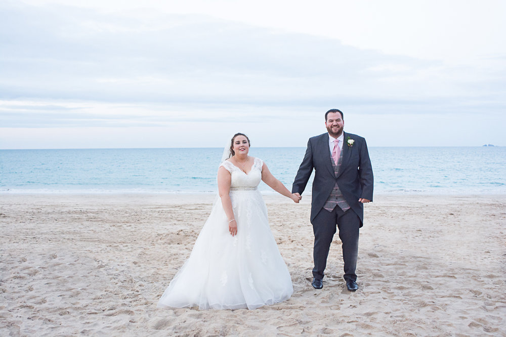 brid and groom hold hands on carbis bay beach cornwall