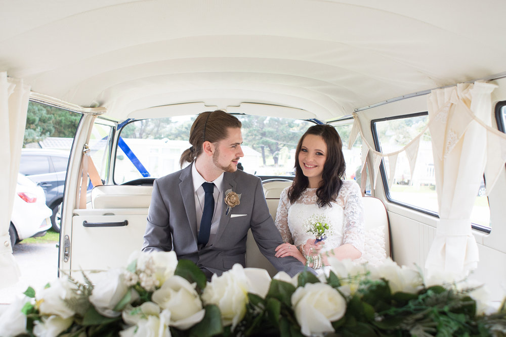 Bride and groom sat in a honey bugs cornwall camper van