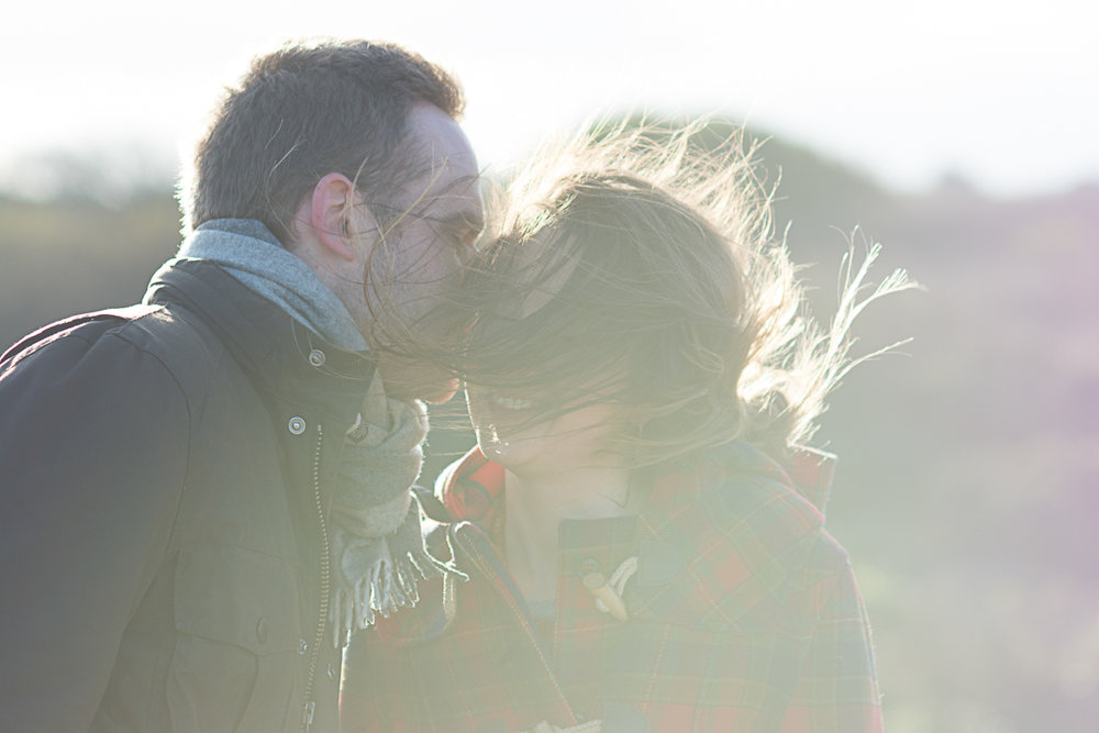 wind blows in her face as he kisses her cheek in st agnes cornwall