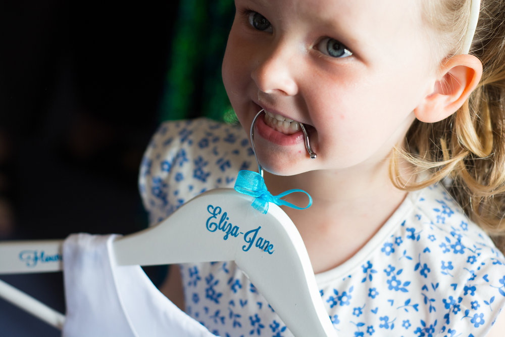 flower girl with personalised clothes hanger in her teeth at the atlantic hotel newquay