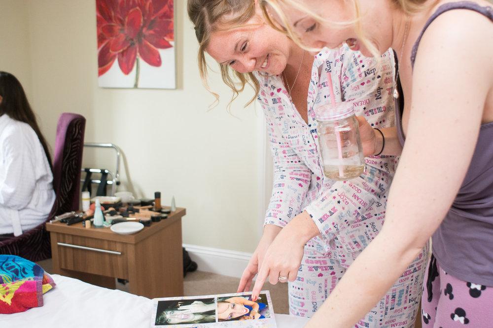 Bridesmaids looking at memory book at Boringdon Hall