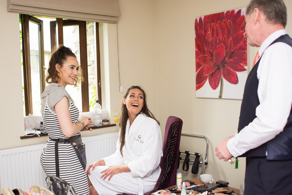 Bride smiling at her dad whilst having her makeup done by the lovely Jasmin Brooke Hallett at Boringdon Hall
