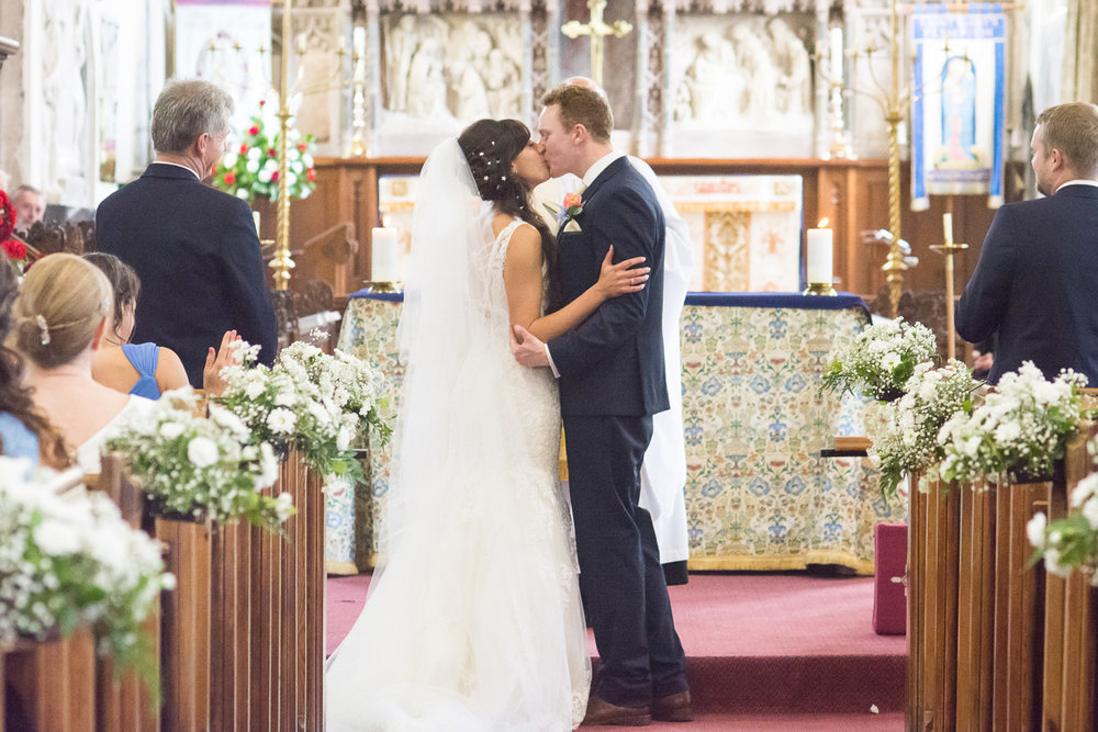 the bride and grooms first kiss at st mary's church plympton plymouth