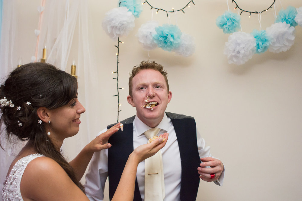 cake cutting gets messy at Boringdon Hall wedding