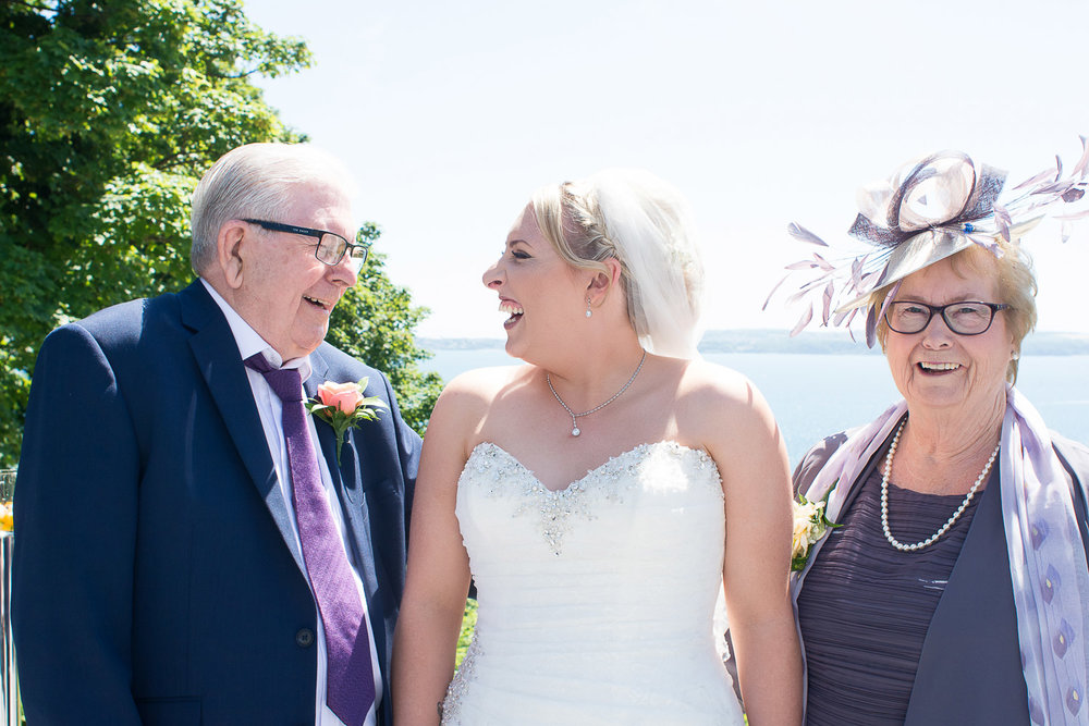the bride and her grandparents smile at each other at the Headland Hotel Torquay