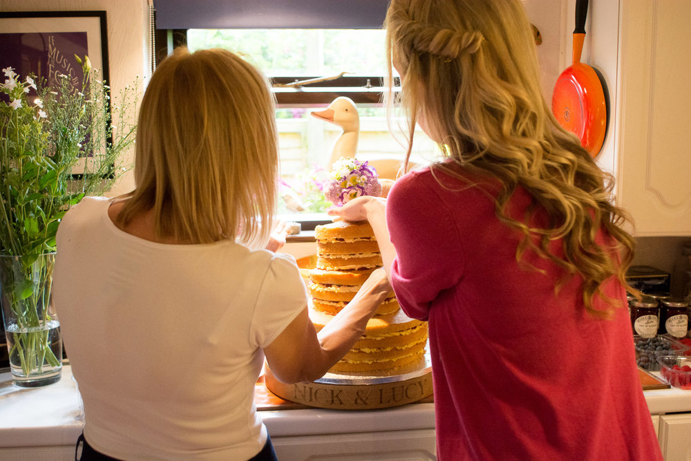 mother and sister of the bride make the wedding cake at wedding yurts wedding in leicestershire